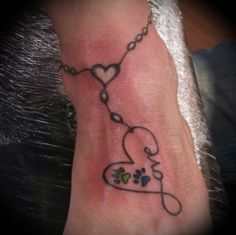 Infinity heart tattoo with a green and blue paw for my dogs on an ankle bracelet.