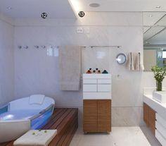 """12– Para o banheiro da proprietária, projetaram um rebaixo no forro sobre a banheira que serve a dois propósitos. Ali, embutiram duas lâmpadas dicroicas com filtro azul . """"Segundo a cromoterapia, é uma luz relaxante"""".13–O nicho que se formou no rebaixo de gesso leva lâmpadas T5, que têm uma luz mais fria, mas com boa iluminação difusa. """"Elas iluminam todo o ambiente. Além disso, são econômicas"""". No banheiro, abaixo, piso e paredes com mámore pigués."""