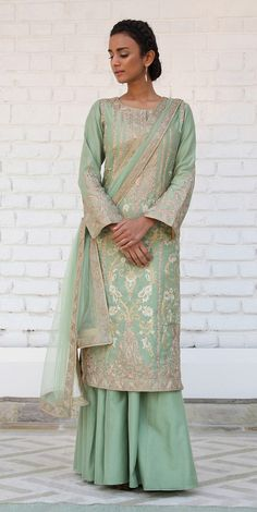 Rimple and Harpreet Narula. Pista green Chanderi silk long shirt featuring delicate aari embroidery in tillaand resham, paired with a soft tulle dupatta and silk sharara.