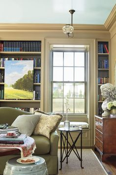 Living Room Bookcase Wall - Senoia Georgia Idea House Tour - Southernliving. Designed to resemble an early-1900s library, the living room contains a wall of floor-to-ceiling bookshelves. Two large double-hung windows punctuate these built-ins, along with cozy window seats below.
