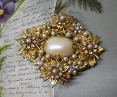 Heres a great looking vintage Miriam Haskell brooch, featuring a border of rhinestone and pearl flowers around a center oval cabochon. It measures 2.13/4 by 2.3/8 and is in exception condition for vintage Haskell; no missing or dark stones, and no wear to pearl finish. Unsigned, but guaranteed to be Haskell (back has 4 separate levels of wired filigree). Thanks for looking. MCP13