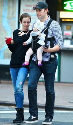 Doting parents: The 31-year-old actress went makeup-free for the stroll while husband John carried their precious cargo in a BabyBjorn