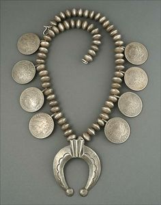 Squash Blossom Necklace   Unknown Navajo Artist.  Circa 1960's   Cast silver naja, the silver beads are made from dimes; date in general to the early 1900s and the dollar coins date from between 1878 and 1921.
