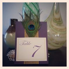 Classy Purple Wedding Table Numbers with Peacock Feature. Each table number is adorned with a single elegant peacock feather and a thick gold ribbon that is perfect for your peacock themed wedding.  Check it out at..  https://www.etsy.com/listing/129464988/classy-purple-wedding-table-numbers-with?