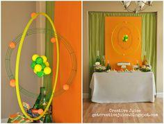 From Creative Juice - Making a giant atom model using a hula hoop and painted Styrofoam balls. Great science decorations for Workshop of Wonders VBS. #firstpresorangeburgvbs