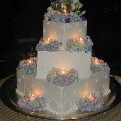 wedding cakes with candles as lights and flowers