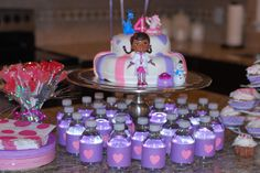 My little Girls Doc Mcstuffins Cake. Super Easy Marshmallow fondant icing- see other pin on this board for recipe. Water bottles are covered with purple construction paper and glittery heart stickers were found at dollar tree (32 count for one dollar). Heart suckers found at Walmart (10 for one dollar).