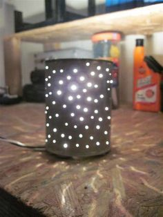 Coffee can with drilled holes, painted white (or any color), battery-operated lights, mason jar inside to hold flowers for a centerpiece. Place on fabric runner or mirror.