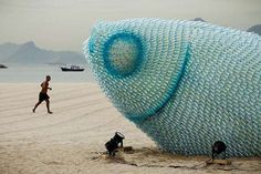 fish sculptures on botafogo beach Rio de Janeiro, Brazil. It's made using abandoned plastic bottles. This incredible creation features humongous fish structures that are lit at night and illuminate the coast.