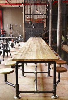 Most excellent swing seat cafeteria table--made from industrial pipes! Truth Coffee by Haldane Martin