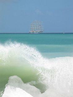 Beach waves and a tall ship on the horizon.