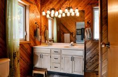 Rustic bathroom with angled wood paneled wall, double sink vanity and lots of lighting.