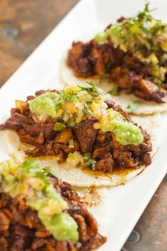 Classic Mexican Tacos Al Pastor 1 white onion 1 peeled fresh pineapple, in crosswise ½-inch slices ½ cup fresh orange juice ¼ cup guajillo chili powder ¼ cup distilled white vinegar 2 teaspoons salt 3 halved garlic cloves 2 small canned chipotle chilies 1½ teaspoons adobo from canned chipotles in adobo 1 teaspoon ground cumin 1 teaspoon dried oregano (Mexican oregano if possible) 2½ - to 3 lbs boneless pork loin, in ½-inch slices ¼ cup chopped fresh cilantro 6 corn tortillas, salsa
