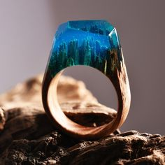 ROCKY LAGOON is a ring made with light oak and light blue jewellery resin.