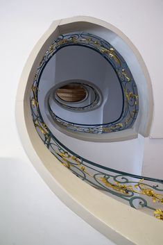 spiral staircase | photo www.nilseisfeld.de Love how the spirals in the wrought metal accentuate the spiral in the whole staircase. The gold details adds enough interest and contrast but doesn't detract from the simplicity.
