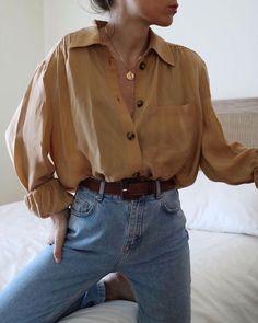 Ample chemise ocre associée à une ceinture de cuir sur un jean donne à l'ensemble une impression de confort et de style