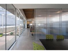 Floor to ceiling glass offers views of the courtyard, while sliding polycarbonate panels create private spaces inside.
