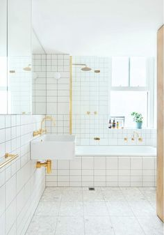 All white bathroom with floor to ceiling tile, a bathtub and shower both with gold hardware.