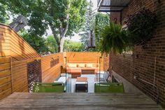 Le terrain en pente au sol irrégulier a été transformé en terrasse à deux niveaux par Montreal Outdoor Living. Le sol est recouvert d'une ardoise pâle qui donne de l'éclat à la cour ceinturée de cloisons de bois. Celles-ci sont animées par des pièces d'acier qui font office d'oeuvres d'art. La terrasse supérieure est attenante à la cuisine, qui attend son tour de rénovation! (Photo Hugo-Sébastien Aubert, La Presse)