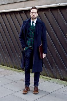 Shop this look on Lookastic:  http://lookastic.com/men/looks/brogues-jeans-belt-overcoat-blazer-tie-long-sleeve-shirt/7138  — Brown Leather Brogues  — Navy Jeans  — Dark Brown Leather Belt  — Navy Overcoat  — Navy and Green Plaid Blazer  — Dark Green Knit Tie  — White Long Sleeve Shirt