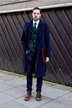 Shop this look on Lookastic:  http://lookastic.com/men/looks/brogues-jeans-belt-overcoat-blazer-tie-long-sleeve-shirt/7138  — Brown Leather Brogues  — Navy Jeans  — Dark Brown Leather Belt  — Navy Overcoat  — Navy and Green Plaid Blazer  — Dark Green Knit Tie  — White Long Sleeve Shirt