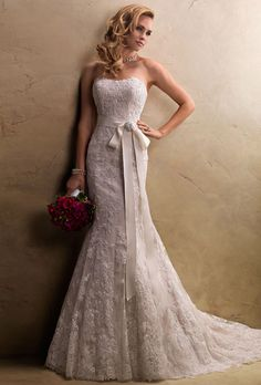 Brides: Maggie Sottero. Classic and elegant with softly dipped neckline and graceful draping, this strapless slim A-line features embellished lace motifs on tulle, grosgrain ribbon belt with Swarovski crystal brooch, and signature corset back closure.��Find a Maggie Sottero Authorized Retailer