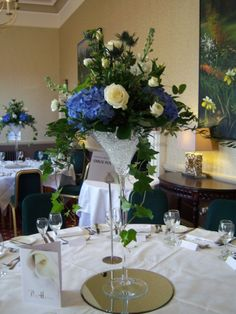 Elegant martini vase arrangement in ivory and blue with hydrangea and roses