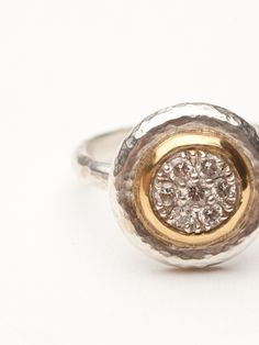 The moonstruck collection is an all time favorite here at APJ. The ring is classic and elegant.  It is made of hand-hammered silver and displays a pave of white diamonds 0.56 ctw.  A 24kt yellow gold circle surrounds the white diamonds. The circular display measures approximately 1.5 cm by 1.5 cm. Size 6.5