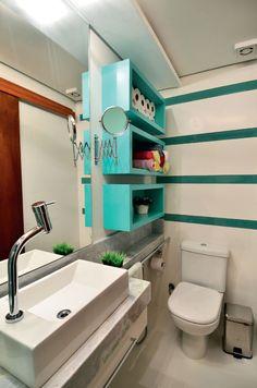 Banheiro organizado e prático. Os filetes de vidro atrás do vaso sanitário contornam os nichos e harmonizam as cores do banheiro.