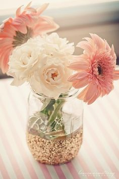 Dip the bottom of a mason jar in glitter and fill with flowers for a pretty, yet cost effective, table centerpiece.