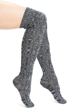 Staying cozy with these chunky cable knit over-the-knee socks featuring a ribbed top for stay-in-place comfort.