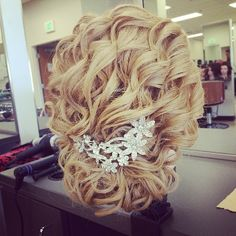 This is a beautiful bridal updo . Love the curls and hair piece . Wedding style
