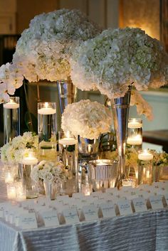 A collection of glass vases at varying heights: Spheres of white hydrangea will alternate with sprays of white Phaleonopsis Orchids and round arrangements of white Garden Roses in glass vases, white column candles, and iridescent glass votive candles add drama to the tabletop. Four Seasons Hotel, Philadelphia {Design: TableArt | Photo: Marie Labbancz}