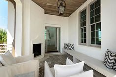 Chic covered patio with corner fireplace and rustic plank ceiling punctuated with steel and glass lantern over long built-in bench dressed in black and white chevron pillows and mosaic tiled floor. Mosaic Tile Fireplace, Stucco Fireplace, Fireplace Outdoor, Covered Back Patio, Covered Decks, White Stucco House, Vacation Rentals By Owner, Stucco Homes, Built In Bench