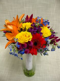 Bright and colorful Bridal bouquet. Flowers include lilies, roses, delphinium, gerbera daisies, celosia and thistle