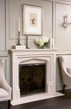 The fireplace is carved limestone and it's by Francois  Co. These sconces are antique and the chairs are by Hickory White.
