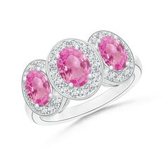 Three-stone engagement rings are timeless classics. Our gorgeous pink sapphire and diamond three-stone ring is a brilliant example of it. The ring features three oval pink sapphires each surrounded by a radiant diamond halo, mounted in dome shape on a 14k white gold band. The center stone overlaps the side ones signifying that your present is what you live the best while cherishing the past and planning for future. With its pink blush, this vintage inspired gemstone ring is a perfect…