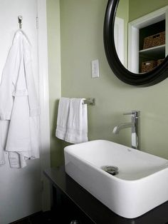 Punch with Paint-  The serene, soft green paint visually expands the small room, and the white sink, towels, and robe are crisp counterpoints to the green walls. A rich brown vanity, framed mirror, and accents add drama.