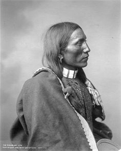 Wah-Be-Git, a Ute man wearing traditional clothing including a blanket, beaded choker necklace, and cloth-wrapped braids. This image was photographed by Rose & Hopkins (Denver, Colo.) at Denver's Festival of Mountain and Plain circa 1896-1899 - History Colorado Collection