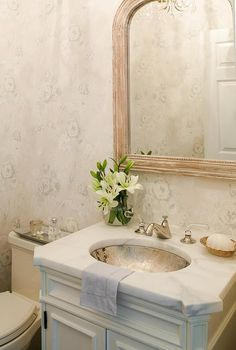 Chic cottage powder room features walls clad in soft and subtle floral wallpaper lined with a whitewashed beaded mirror over a white washstand topped with honed white marble fitted with an oval hammered metal sink.