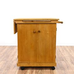 This server cart is featured in a solid wood with a glossy maple finish. This american traditional style kitchen island has a towel rack, cabinet w/ interior shelving and pull-out trays. Perfect for serving and preparing food! #americantraditional #tables #beveragecarts #sandiegovintage #vintagefurniture