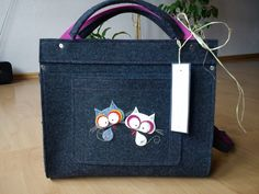 A cute bag (briefcase) with two cats on it, made almost entirely with felt.   You can order such on Etsy :).