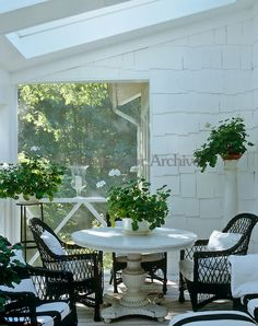 Black wicker chairs make an elegant statement in this all-white garden room where the walls have been covered in white-painted shingles