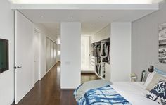 """In the bedroom, an open closet with built-in shelving leads to the master bathroom. Thinking of all the loft's components as part of a whole was critical to the renovation. """"The space is clean and simple, but that is only possible because of the attention paid to eliminating visual clutter that often comes from typical detailing,"""" Breitner says. """"The HVAC, floor outlets, door detailing, wall reveal base, recessed glazing channel, and radiator covers could look like clutter. We integrated it…"""