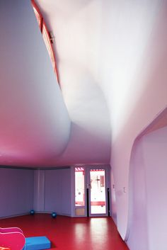 Sarreguemines Nursery in France designed by Michel Grasso - features an organic moulded ceiling and walls, with high clerestory window openings - allowing light to filter in.