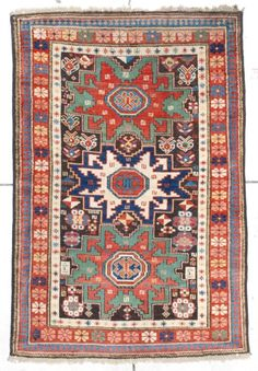 """This antique Leshgi Star Shirvan is dated 1310 for 1893.  It measures 3' 4"""" x 4' 7"""". It is a very lovely antique Shirvan dated in two places. It has three stars, two red on green and one ivory on dark blue which are on a brown ground .   The rug is very asymmetric with many small figures such as small S motifs, quartered diamonds, flower blossoms, and palmettes. It has an ivory minor border with eight pointed stars.  It has a rust major border with flower blossoms.  It has a reciprocal red…"""