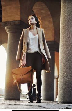 A perennial classic, the long camel coat, paired with a unisex leather bag.