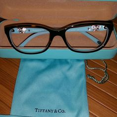 Authentic Tiffany & Co. Butterfly frames glasses Authentic Tiffany & Co. Butterfly frames, glasses case, bag, and wipe. All with Tiffany & Co.  On it.   In great condition. Super cute. Teal green and deal and light brown with rhinestone butterflies on each side. Made in Italy.  Shell case has normal wear on it. Light scratches on it.  Not very noticeable at all.  Please lmk if you have any questions. Reasonable Offers accepted. Thank you for shopping my closet. :) Tiffany & Co. Accessories…