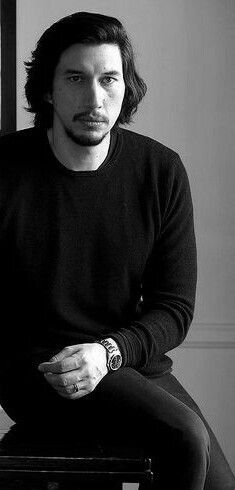 Adam with longish hair and goatee all in black, black and white photo.