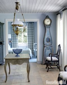 The palette shifts to blues and grays in the guesthouse. A gaslit Swedish Art Nouveau chandelier hangs above a German Rococo table in the stair hall. The antique Mora clock from Napoleon Inredningar is painted in a beautiful Swedish blue — a deeper iteration of the blue on the walls. Bedroom curtains in Chelsea Edition's Large Check.